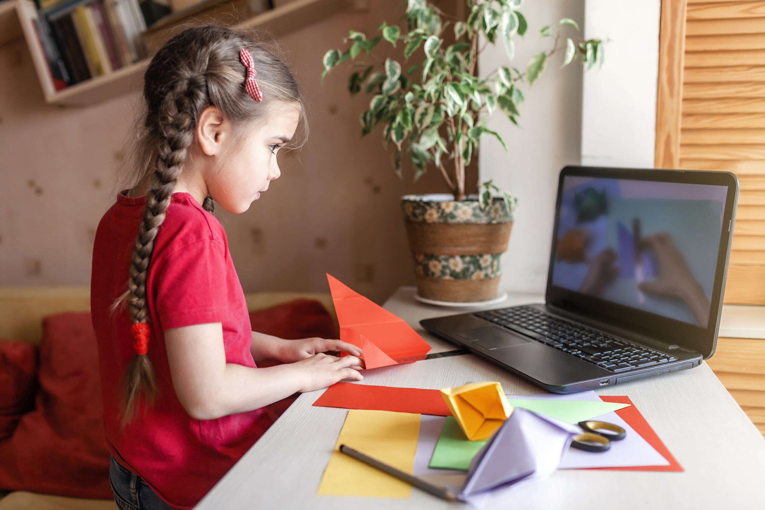 Girl doing origami fish with colour paper looking video on laptop, online workshop and distant education